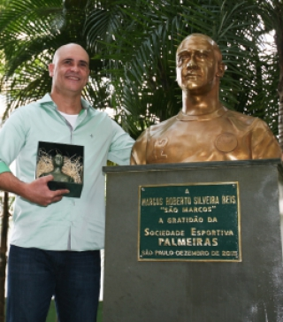 Marcos ao lado do busto no Palestra